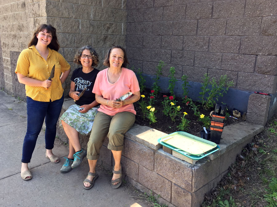 Volunteers who helped plant flowers in a prepared bed as part of the ceremonial flower planting during the Pop Up Community Event